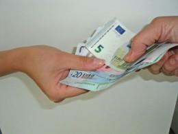 Geldscheine gehen von einer Hand in die Andere