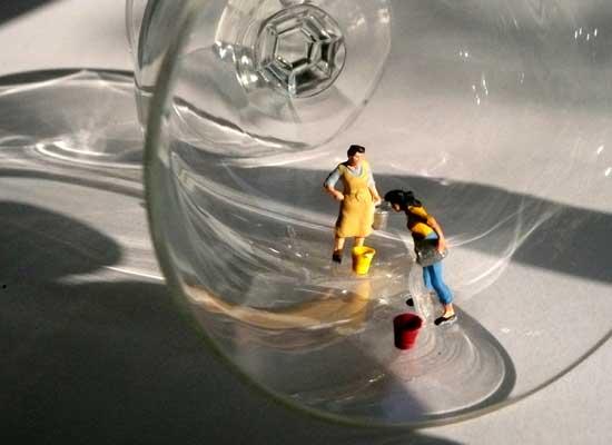 Miniatur-Hausfrauen putzen in einem Glas