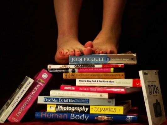 Nackte Füße auf Bücherstapel