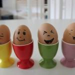 Vier Eier mit Gesichtern in Eierbechern