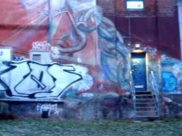 Eine Wand mit Graffiti und einer Blauen Tür