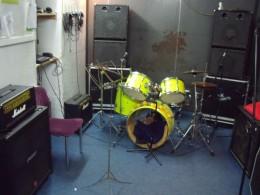 Ein Neon Gelbes Schlagzeug in einem kleinen dunklem Raum