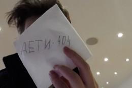 """Jugendlicher hält Papier mit der Aufschrift """"Deti 404"""" vor seinem Gesicht"""