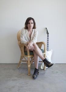 Frau sitzend mit Gitarre im Hintergrund
