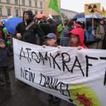 """Demonstranten halten ein Stoffplakat mit dem Slogan """"Atomkraft? Nein Danke!"""""""