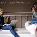 Zwei Frauen auf dem Bett sitzend. Eine mit Laptop, die andere mit einer Fotokamera