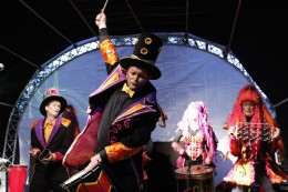 Es ist eine Samba Percussion Band aus Bremen auf der Bühne abgebildet. Diese sind verkleidet wie Waldfeen und Zauberer.