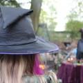 Es ist ein Kind mit einem Hexenhut von hinten zu sehen. Im Hintergrund befindet sich verschwommen eine Hexe die aus ihrem Buch liest.