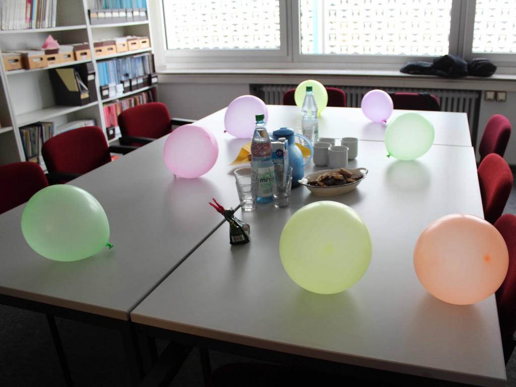 Konferenzraum mit Tischen und bunten Luftballons