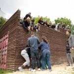 Zu sehen ist eine Gruppe die vor einer hölzernen Mauer steht. Einige befinden sich über der Mauer.