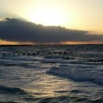 Sonnenuntergang am Meer mit dunkler Regenwolke