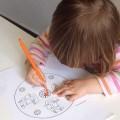 Kind über Malpapier gebeugt