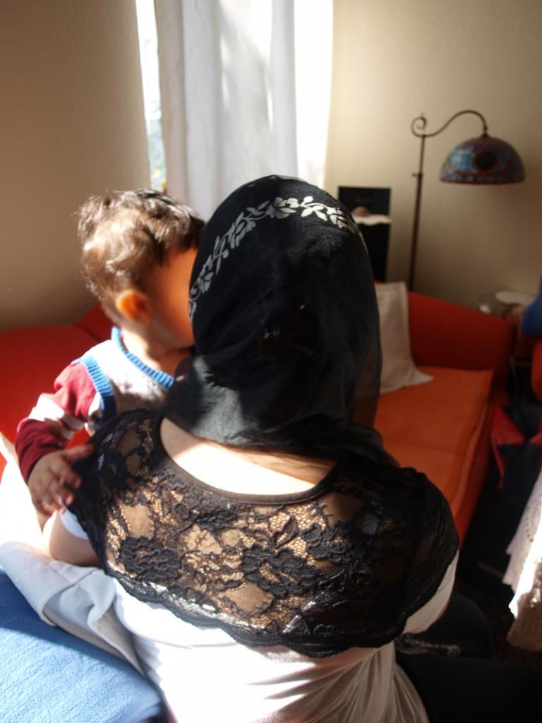 geflüchtete Frauen, Rückenansicht einer jungen Frau mit Kind
