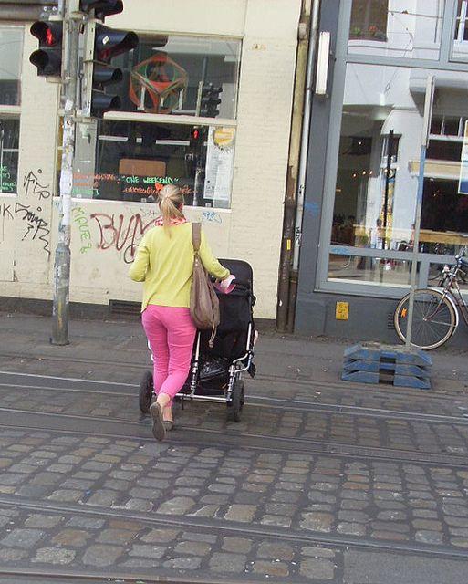 Frau mit Kinderwagen überquert eine Straße