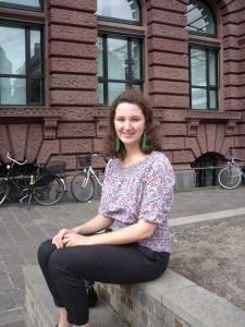 Junge Frau auf Steinbank sitzend vor Backsteingebäude