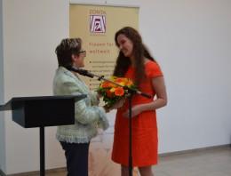 Eine Frau überreicht einer zweiten eine Blumenstrauß