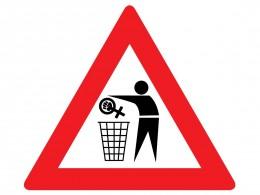 Mensch schmeißt Feminismussymbol in den Müll