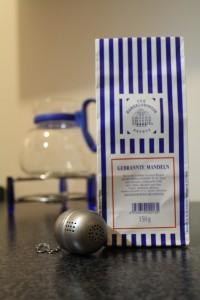 """Zu sehen ist ein """"Gebrannte Mandeln"""" Tee mit einem Teesieb und einer Tee-Kanne im Hintergrund."""
