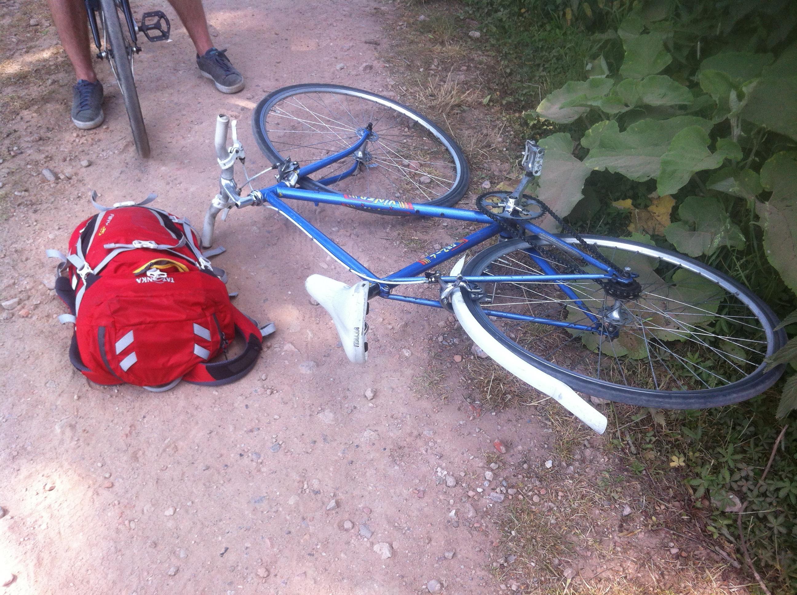 Liegendes Fahrrad und Rucksack