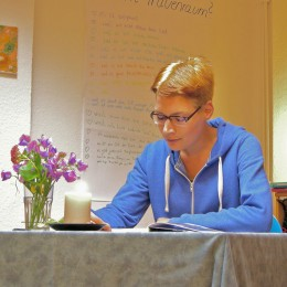 Eine Frau sitzt am Tisch und liest aus einem Buch vor