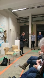 Rednerin steht vor Publikum in der Galerie