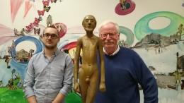zwei Männer neben einer Bronzefigur