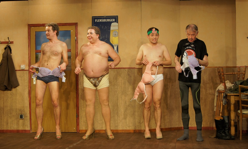 vier Männer mit in Pumps und Unterwäsche auf der Bühne