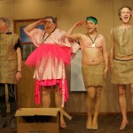 vier Männer auf der Bühne in Kleid und Rock