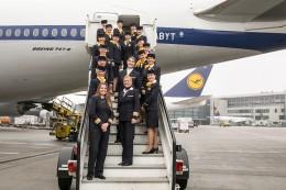 Frauencrew der Lufthansa posieren auf Treppe vorm Flugzeug