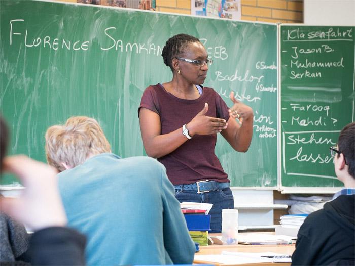 Junge Frau spricht vor einer Klasse