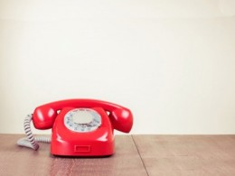 rotes Telefon mit Wählscheibe auf Holztisch