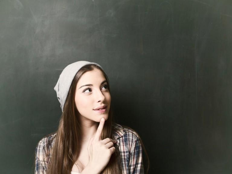 Nachdenkliche junge Frau vor einer Schultafel