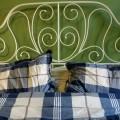 Weißes Bett mit blauen Bettbezug vor olivgrüner Wand