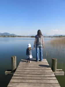 Frau mit Kleinkind auf einem Steg am See