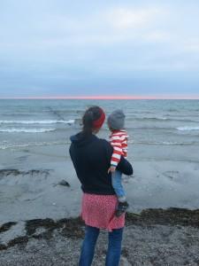 Kind auf dem Arm der Mutter mit Blick auf das Meer