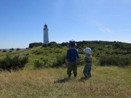Zwei Kleinkinder vor einem Leuchtturm