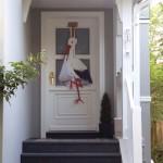 Hebammen Storchenfigur an einer Haustür
