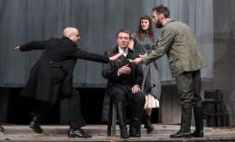 Hexenjagd Ein Mann sitzt auf einem Stuhl, rechts und links von ihm argumentieren zwei Männer.