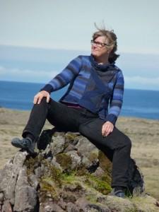 Frau sitzt auf einem Felsen