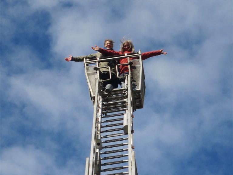 Zwei Frauen am oberen Ende einer Feuerwehrleiter vor blauem Himmel