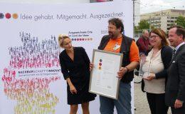Mann mit orangfarbenen T-shirt wird ausgezeichnet bei Preisverleihung und hält Urkunde