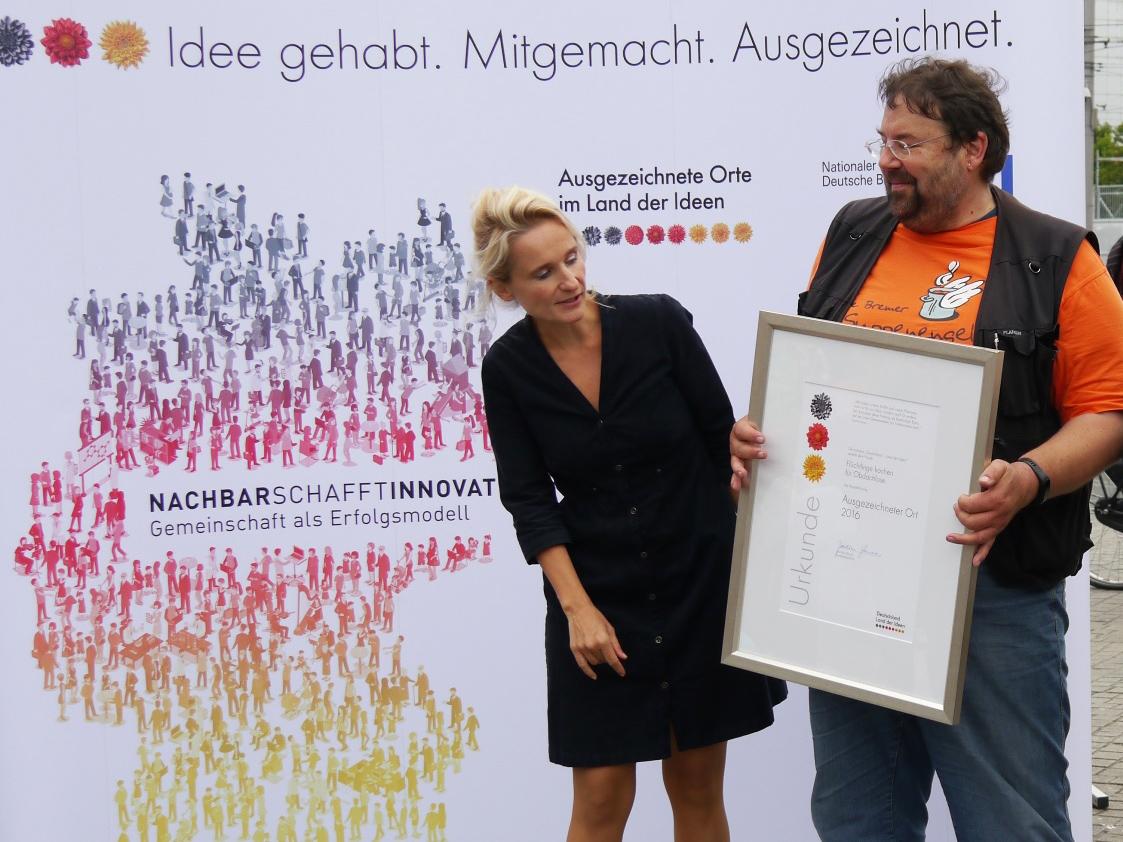 blonde Frau und Mann mit Urkunde