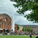 Menschen sitzen an Biertischen vor dem Bremer Hauptbahnhof