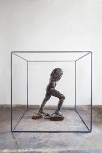 Holz-Skulptur ohne Kopf in einem Metallkäfig