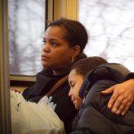 Ein Kind lehnt sich während der Busfahrt an seine Mutter, die aus dem Fenster schaut und es umarmt