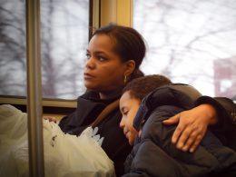 Stressbelastung für Mütter, Ein Kind lehnt sich während der Busfahrt an seine Mutter, die aus dem Fenster schaut und es umarmt