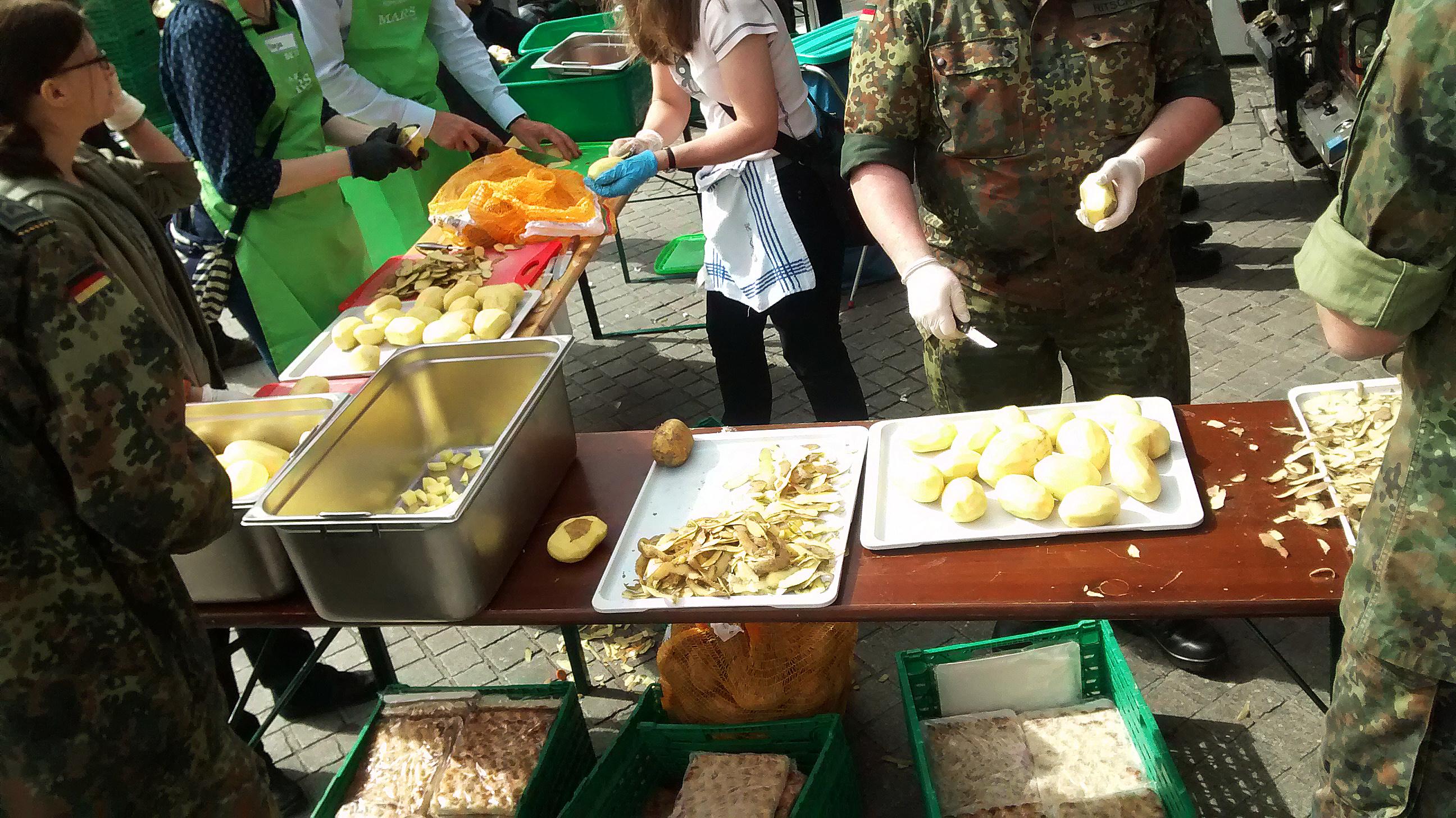 Freiwillige in Schürzen und Militäruniformen schälen Kartoffeln