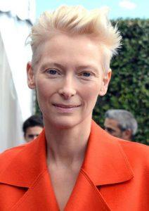 Porträit von Tilda Swinton in orangefarbener Jacke