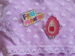 """Zwei Anstecker, einer liest sich """"Free Manko"""", der andere zeigt eine gezeichnete Vulva"""
