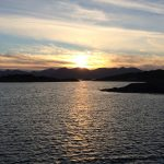 Sonnenuntergang über einem Gebirge, im Vordergrund das Wasser eines Fiordes